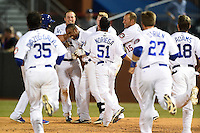 Chattanooga Lookouts first baseman O'Koyea Dickson (7) gets mobbed by teammates after a walk off base hit during a game against the Birmingham Barons on April 24, 2014 at AT&T Field in Chattanooga, Tennessee.  Chattanooga defeated Birmingham 5-4.  (Mike Janes/Four Seam Images)