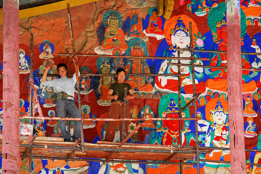 Tibetan artists repaint old rock carvings of important Buddhist figures on a cliff face along the Lingkhor pilgrim circuit as it ascends Chagpo Ri mountain, Lhasa, Tibet, China.