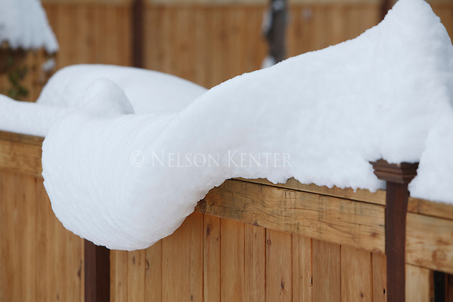 Snow begins to hang off of a fence top after a deep snowfall