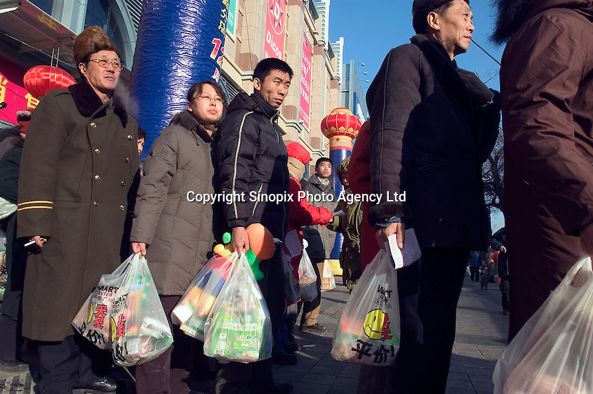 Consumers line up with commodities after shopping for the regular bus of Wal-Mart in a newly opened Wal-Mart Supercenter in Harbin, Heilongjiang province, China..27-DEC-04