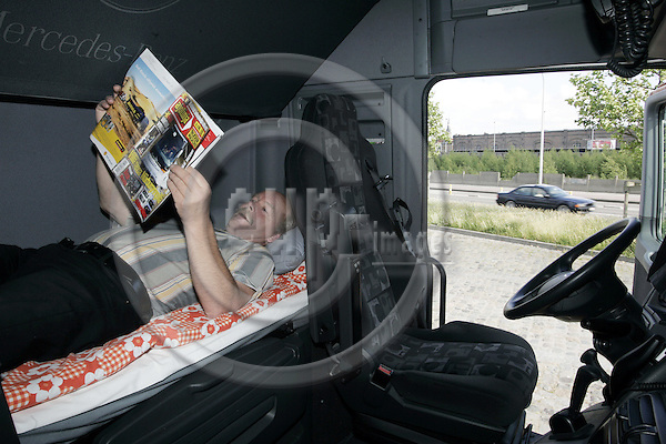 ANTWERPEN - BELGIUM - 04 JUNE 2005 -- Finnish truck drivers passing through Antwerp. -- Kari in the cockpit his truck reading a magazine during his afternoon siesta. --PHOTO: JUHA ROININEN / EUP-IMAGES