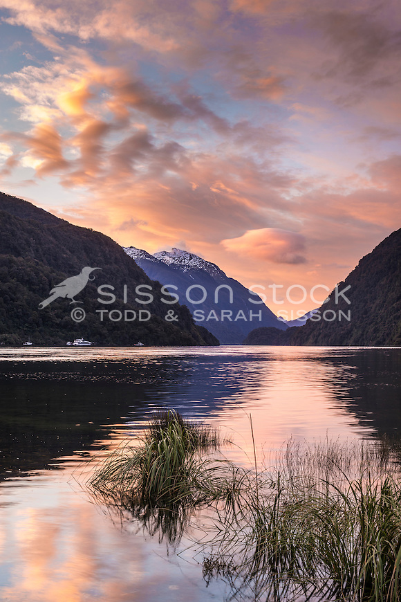 Dramatic clouds in the evening are reflected in calm waters at Doubtful Sound, Fiordland National Park, Southland, New Zealand - stock photo, canvas, fine art print