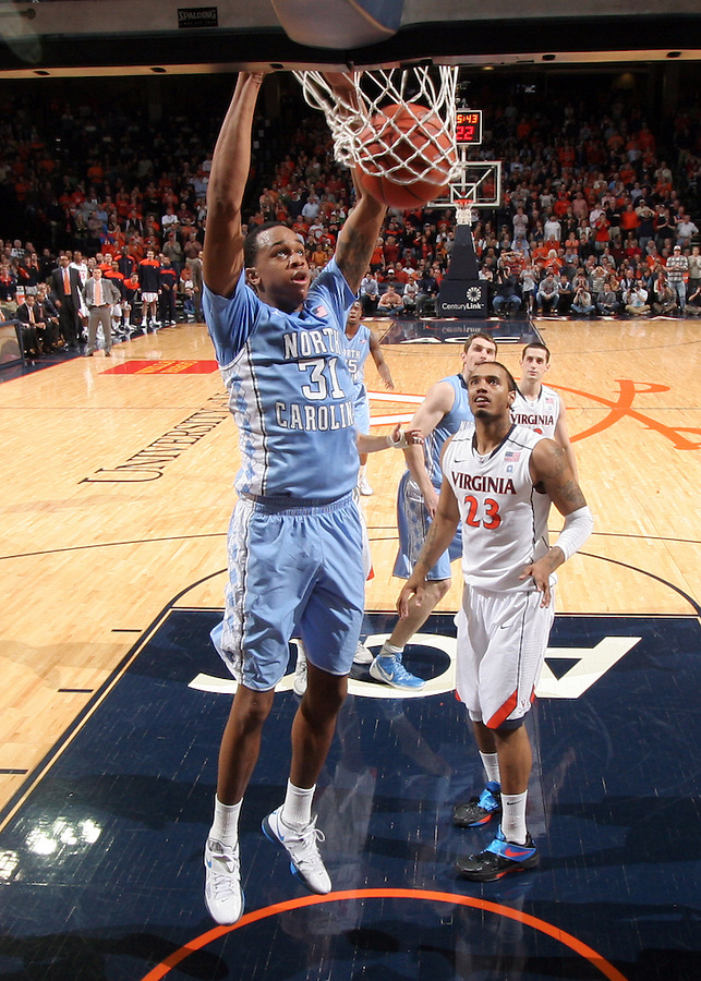 North Carolina Tar Heels forward John Henson (31) dunks the ball in front of Virginia Cavaliers forward Mike Scott (23) during the game in Charlottesville, Va. North Carolina defeated Virginia 54-51.