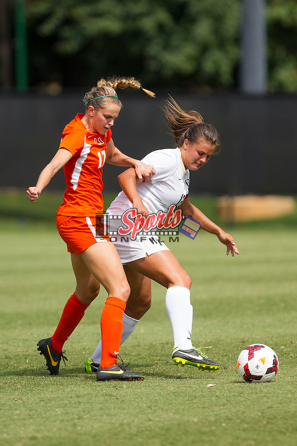 Katie Stengel (12) of the Wake Forest Demon Deacons battles for the ball against Gracie Lachowecki (17) of the Miami Hurricanes at Spry Soccer Stadium on September 15, 2013 in Winston-Salem, North Carolina.  The Deacons defeated the Hurricanes 4-0.   (Brian Westerholt/Sports On Film)