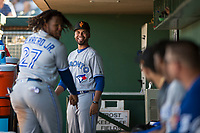 Surprise Saguaros position coach Andy Fermin (2) and Vladimir Guerrero Jr. (27), both of the Toronto Blue Jays organization, play a game in the dugout during an Arizona Fall League matchup against the Scottsdale Scorpions at Scottsdale Stadium on October 26, 2018 in Scottsdale, Arizona. Surprise defeated Scottsdale 3-1. (Zachary Lucy/Four Seam Images)