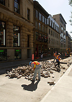 Montreal (Qc) Canada - June 23 2009 - city workers install old pavement stones on saint-sulpice in Old  Montreal
