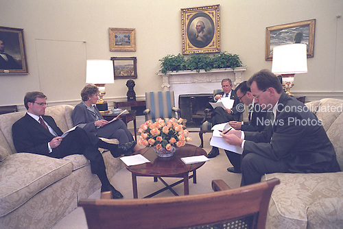 Preparing for an address to the nation and a joint session of Congress, United States President George W. Bush discusses his speech with Counselor Karen Hughes and speechwriters John McConnell (far left), Director of Presidential Speechwriting Mike Gerson (center, right) and Matt Scully (far right) in the Oval Office of the White House in Washington, D.C. on Tuesday, September 18, 2001..Mandatory Credit: Tina Hager - White House via CNP.