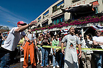 Erk Erk Espinoza, (R) and Anders Miller, (C), both of Pike Place Fish Market, look on as J.J. Swanton, (L), throws a fish in the salmon-tossing contest held in honor of the 100th anniversary of the Pike Place Market in Seattle. The public market is famous for its fishmongers who send fish flying through the air after they are purchased by customers. Swanton was the overall winner of the contest, which judged contestants' talent at both throwing and catching the slippery fish. For a century, the Pike Place Market, has become a city institution and a national attraction, bringing in over a million tourists a year. .Jim Bryant Photo. ©2010. ALL RIGHTS RESERVED.