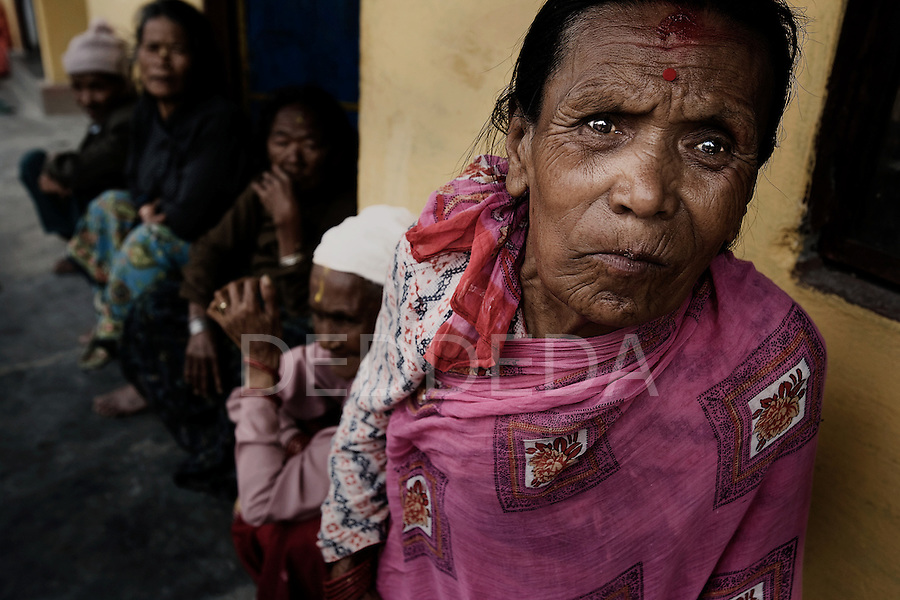 """An elderly woman looks on at an """"Aged Shelter"""" in Pokhara, Nepal. The shelter is a place for seniors to live who have no other family members to look after them. The shelter has no running water, the cooking is done over a fire, there are no nurses or doctors, no heating, and no medication available for the residents."""