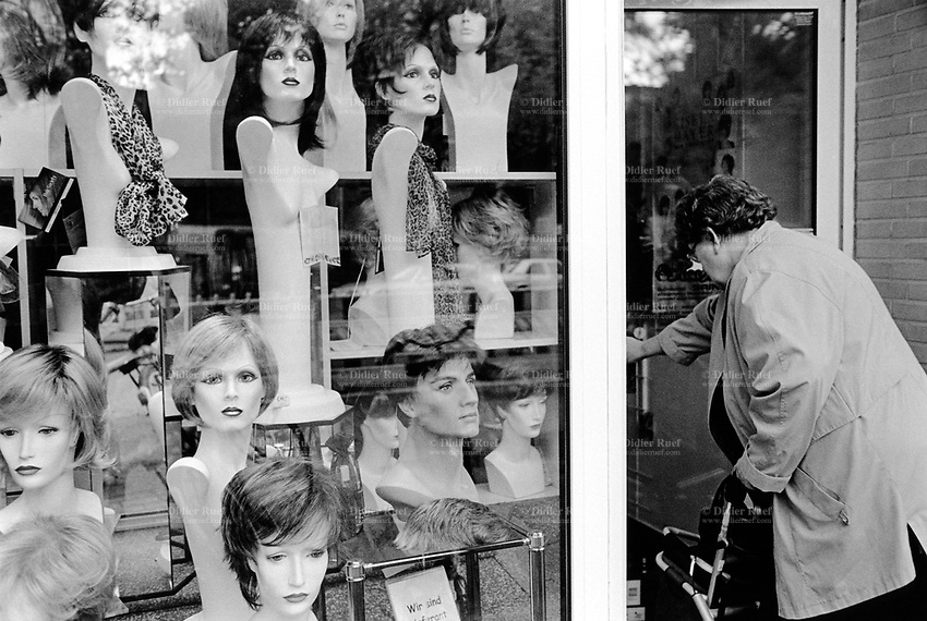 Germany. Hamburg. Daily life. An elderly woman enters a hairdressing salon. Wigs on mannequins, rows of wigs on shelves behind glasses. Hamburg, officially Free and Hanseatic City of Hamburg, is the second largest city in Germany and the seventh largest city in the European Union. 24.05.13 © 2013 Didier Ruef