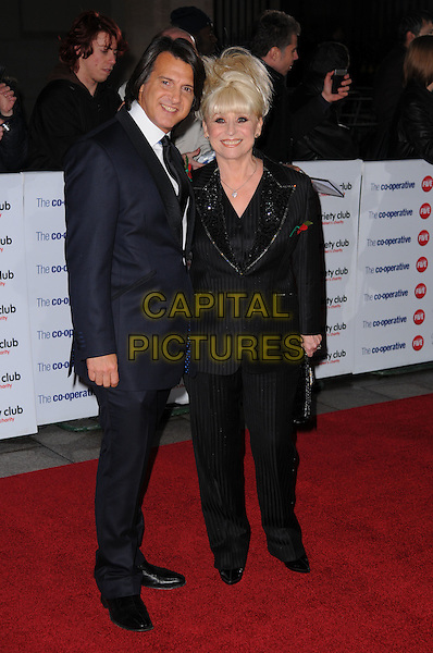 SCOTT MITCHELL & BARBARA WINDSOR .The Co-operative Variety Club Showbiz Awards, Grosvenor House Hotel, Park Lane, London, England, UK, .14th November 2010. .full length suit clutch bag striped pinstripe suit smiling black couple navy blue husband wife married jacket shirt .CAP/CAS.©Bob Cass/Capital Pictures.