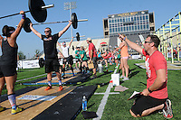 NWA Democrat-Gazette/FLIP PUTTHOFF<br /> CROSSFIT COMPETITORS<br /> Jeff Ecker (right) judges a weight-lifting event  Saturday Sept. 5 2015 at the CrossFit Mid-America Championship at Tiger Stadium in Bentonville.  About 300 athletes from several states competed in weight-lifting and endurance events. The championship is a benefit for Guardians for Heroes, which helps veterans purchase gym memberships and exercise equipment, said Lee Kelly, owner of CrossFit NWA. Events continue at 8 a.m. today at the stadium. The public is invited to watch at no charge, Kelly said.