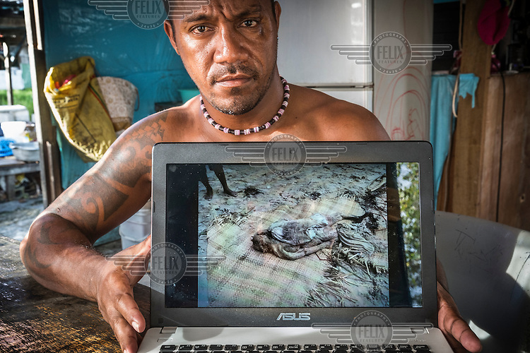 Nelly Seniola, 35, extension officer in the Tuvaluan fisheries department, shows a photograph on his laptop of a corpse that was washed out of a cemetery by a storm surge. Nelly says: 'There were many dead bodies, skulls and bones floating around. Pigs and chickens started to eat some of the bodies. We received a radio message from the capital, that we had to kill those animals, as they could spread diseases.'<br /> Category 5 tropical Cyclone Pam hit the Central and Northern island groups of Tuvalu between March 10 and 11, 2015. 3-5 metre tidal surges swept across many of the northern atolls, destroying roads, houses and cemeteries. Nui Atoll was affected by storm surges caused by Cyclone Pam in which 12 houses were completely destroyed and 110 homes badly damaged. 71 families (40% of the population) from Nui were displaced and were living in evacuation centres or with other families. According to Tuvalu Prime Minister Enele Sopoaga estimated 45 percent of the nation's nearly 10,000 people were displaced.