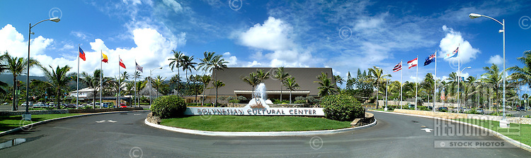 """Panorama of the popular tourist attraction, Polynesian Cultural Center on Oahu's north shore, featuring the """"""""thatched roof"""""""" entrance surrounded by palm trees. Bright blue sky with wispy clouds in background."""