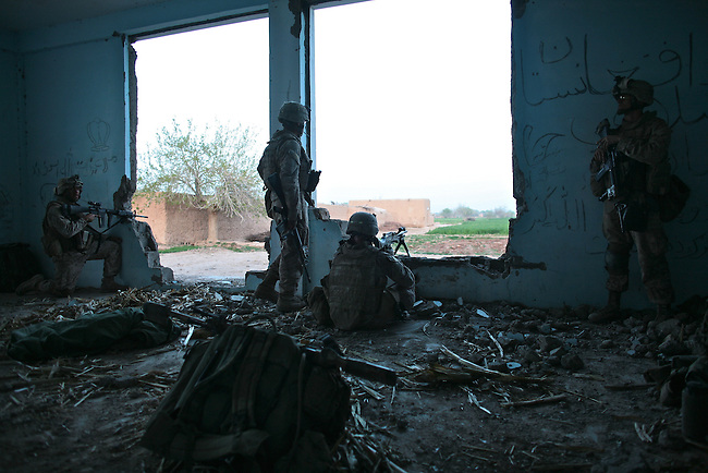 With their wounded comrade safely aboard a medevac helicopter, Marines from Company L,  3rd Battalion, 6th Marine Regiment stay vigilant in case Taliban fighters renew their attack on the Marines' position inside an abandoned school near Marjah, Afghanistan. March 10, 2010. DREW BROWN/STARS AND STRIPES