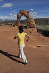 Woman hiking at Delicate Arch in Arches National Park, Moab, Utah, USA. .  John offers private photo tours in Arches National Park and throughout Utah and Colorado. Year-round.