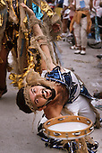 Rio de Janeiro, Brazil. Carnival, bearded musician with tambourine, smiling and spinning the tambourine.