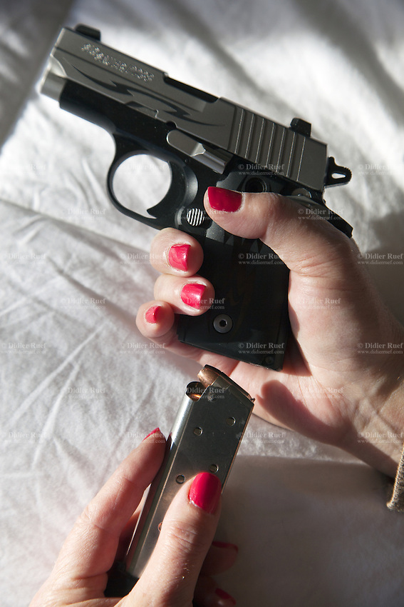 """USA. Arizona state. Scottsdale. Carrie Lightfoot is the founder and CEO of """"The Well Armed Woman. Where the Feminine and Firearms Meet"""" which sell online resources for women gun owners. She stands in her bedroom and holds a handgun SIG SAUER P238 .38 in her hands. The SIG SAUER P238 .380 Auto Pistol features a stainless-steel slide with slide serrations and an anodized alloy beavertail-style frame. The single-action pistol has an extended 7-round magazine capacity. Carrie Lightfoot has finished loading the gun with bullets and is ready to used it as concealed carry firearm. A firearm is a portable gun, being a barreled weapon that launches one or more projectiles often driven by the action of an explosive force. Most modern firearms have rifled barrels to impart spin to the projectile for improved flight stability. The word firearms usually is used in a sense restricted to small arms (weapons that can be carried by a single person). The right to keep and bear arms is a fundamental right protected in the United States by the Second Amendment of the Bill of Rights in the Constitution of the United States of America and in the state constitutions of Arizona and 43 other states. 28.01.16 © 2016 Didier Ruef"""
