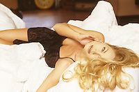 Photo of a playful woman on a bed in black lingerie looking at her boyfriend.