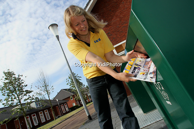 Foto: VidiPhoto..DUIVEN - Storemanager Audrey Sinderdinck van Ikea in Duiven gooit Ikea-gids 2010 in de papierbak.