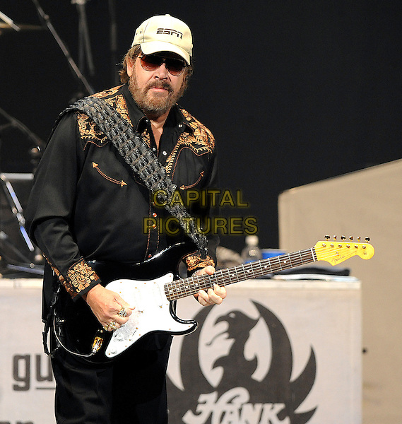 HANK WILLIAMS JR..Musician Hank Williams Jr. performs live as his 2010 Rowdy Friends Tour makes a stop at the RBC Center, Raleigh, North Carolina, USA..October 23rd, 2010.stage concert live gig performance music half length black shirt white baseball cap hat beard facial hair sunglasses shades guitar.CAP/ADM/MOO.© Moose/AdMedia/Capital Pictures.