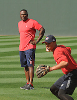 Carlos Febles, manager of the Greenville Drive, left, works with second baseman Mookie Betts (7) during extra infield practice during Media Day just prior to the start of the 2013 season on Tuesday, April 2, 2013, at Fluor Field at the West End in Greenville, South Carolina. (Tom Priddy/Four Seam Images)