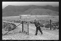 A Chinese security guard closes the gate of the Helan Mountains Forest Park in Alashan Zuoqi , Inner Mongolia, 2015.