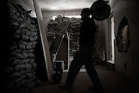 a US non commisioned officer from 1st platoon Alfa company, 3-103d armor regiment, 28th US National Guard Division lifts weights to spend some time while on a three day rotation on OP ( observation post) HOTEL, a five floors building in Western Ramadi, capital of the Anbar province, Iraq on the day following the national elections FRI DEC 16th 2005..Nor US military or Iraqi Army  were in charge of securing the Ramadi polling stations during the elections. they simply conducted daily routine patrols hoping that the insurgency would keep its promise not to attack on this day. US forces watched the voting form observation posts located at the boarder of the city. OP HOTEL is one of them on code name route MICHIGAN. On August 15 2005 a suicide bomber detonated a truck filled with more than 500 KGs of explosives in front of the main entrance. Due to heavy fortification no US soldiers suffered deadly wounds. The OP scans a strip of road on which more than 60 improvvised explosive devices are found or detonated every month. life at the HOTEL is quite simple. US squads rotate on the numerous observation posts in the building every six hours for three hours. sniper teams keep the area constantly in their rifle scopes. it's a 24 hour, non stop process. hot meals are driven by platoon members once a day. living conditions are miserable. the worst part of it all is being trapped in a fortified buliding, where the only windows available are the ones out of which they  shoot all their weapons. these soldiers saw the elections through these holes, with their body armors and their night vision nodes, through their rifle scopes and with the constant soundtrack of bombs, mortars and small arms fire always present in the background.