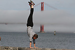 Marin a tourist from Frances performs handstands off a wall at the Saint Francis Yacht Club in San Francisco, CA.