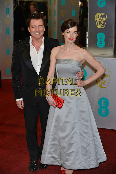 Charles Worthington & Jessica Raine.Arrivals at the EE British Academy Film Awards at The Royal Opera House, London, England..10th February 2013.BAFTA BAFTAS full length strapless white shirt black suit hand on hip dress silk satin red clutch bag shoes .CAP/PL.©Phil Loftus/Capital Pictures
