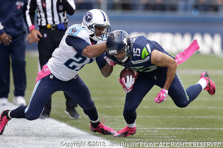 Seattle Seahawks wide receiver Jermaine Kearse (15) is thrown out of bounds by Tennessee Titans safety George Wilson (21)after catching a pass for a nine year gain in the third quarter at CenturyLink Field in Seattle, Washington on  October13, 2013.  The Seahawks beat the Titians 20-13.   ©2013. Jim Bryant Photo. All Rights Reserved.