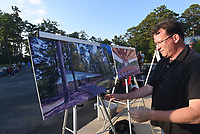 NWA Democrat-Gazette/FLIP PUTTHOFF <br /> SHELTER FOR LEARNING<br /> Rich Brya, a board member with Friends of Hobbs, arranges Saturday June 10 2017 art prints of an education pavilion to be built near the visitor center at Hobbs State Park-Conservation Area. Friends of Hobbs hosted a gala Saturday evening to unveil the design of the pavilion that will serve as an outdoor classroom and a covered outdoor venue for park events. Construction will begin this summer. The $500,000 project is funded by Friends of Hobbs with a matching grant from Arkansas State Parks, Brya said. Location of the pavilion is in the picnic area just east of the visitor center.The event featured a concert by National Park Radio, food, and prize drawings.