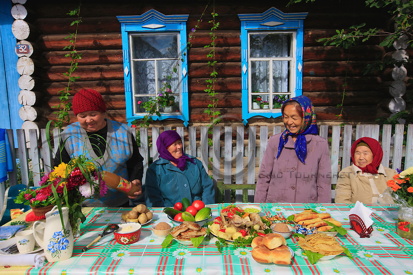 "In front of an isba, babushkas in multi-colored scarves compete for the prize of flowering village.  The national drink of Bashkir is a sort of mead made from plants called ""hitabalé""."