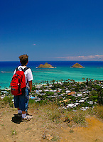 A young boy (age 9) enjoys an elevated view of the Moku Lua islands and Lanikai Beach from the Kaiwa ridge trail. Located south of the town of Kailua, windward oahu.
