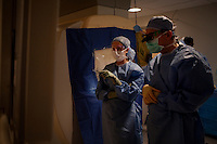 San Francisco, California, January 6, 2011 - From left, Dr. Ellen Air, a clinical fellow, and University of California San Francisco Medical Center neurosurgeon Dr. Philip Starr look at real time scans of patient Linda Sharp during her iMRI surgery at UCSF Medical Center. The MRI machine photographs the patient during the surgery allowing the doctors operating to view the procedure as well as support doctors and technicians to monitor from an outside room.  The iMRI procedure uses Deep brain stimulation (DBS), which has been used for over a decade to treat movement disorders such as Parkinson's disease, essential tremor, and dystonia. DBS uses a pulse generator implanted in the chest, similar to a pacemaker, to deliver pulses to specific regions of the brain via a permanently implanted electrode. In the U.S., DBS is normally done while the patient is awake, because the surgeon needs to induce the symptoms (like the involuntary movements of Parkinson's) to know if he's in the right place, and if the patient is unconscious, the symptoms can't be induced. Many patients find it hard to tolerate. Their head is clamped in a frame, they're aware of their surroundings, and the surgeon is deliberately producing tremors and twitches while they lie there...Interventional MRI (or iMRI) allows surgeons to implant these electrodes while the patient is unconscious taking advantage of MR imaging in real time by performing procedures inside the scanner itself. Doctors Paul Larson and Philip Starr were both involved with this technology during its development in the 1990s. In 2002 they began to think about how to perform DBS using this technique at UCSF. Working with Alastair Martin PhD in the Department of Radiology, Jill Ostrem MD in the Department of Neurology, and others, they developed a technique of implantation using a modified but commercially available skull-mounted aiming device and custom-made, MR-compatible surgical instruments.