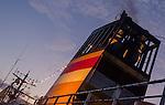 A colorful PELNI ship smoke stack against an evening sky.