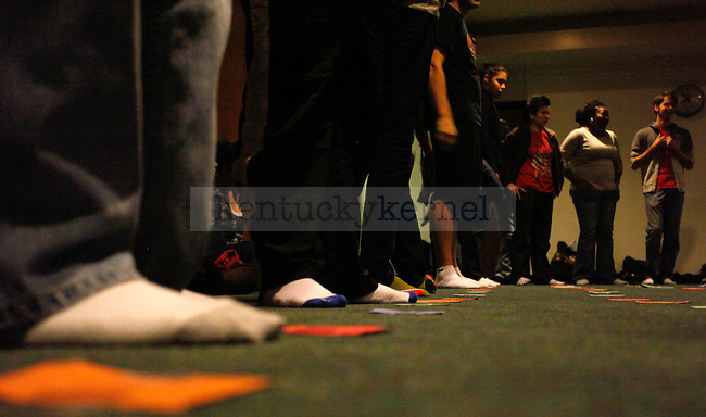 People stand around the mat waiting for the game to start during the Ultimate Twister Gay-Straight Alliance event held in room 357 of the Student Center Thursday night. The event is held annually as part of the Coming Out Week put on by the OUTsource and GSA. Members make a large twister mat by taping colored paper squares for twister spots on the floor.   Photo by Zach Brake | Staff