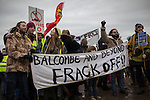 """© Joel Goodman - 07973 332324 . 26/01/2014 . Salford , UK . A banner that reads """" Balcombe and beyond frack off """" . Approximately 500 protesters march to an iGas fracking exploration site at Barton Moss , Salford , today (Sunday 26th January 2014) . They walk along the A57 road , blocking traffic as they do . A long term protest camp has been established on an access road leading to the site and today (26th January) protesters from other areas of the country travelled to the site to join with other protesters against fracking . Photo credit : Joel Goodman"""