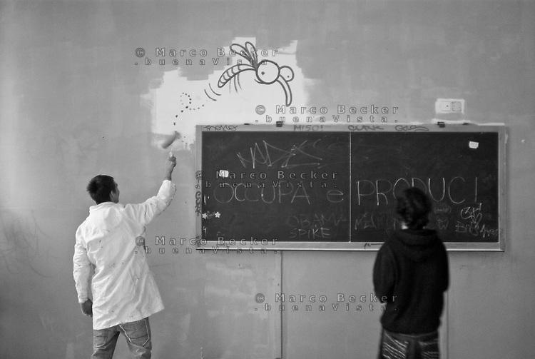 Milano, occupazione e autogestione del Liceo Artistico Statale di Brera per protestare contro la riforma dell'istruzione. Studenti dipingono le pareti di una classe. Sulla lavagna la scritta Occupa e produci --- Milan, occupation and self-management of Brera art high school as a protest against the school reform. Students paint the walls of a classroom. On the blackboard the writing Occupy and produce