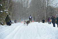 Nathan Sterling passes by University Lake during the first day of the World Championship Sled Dog Races, a highlight of the 2013 Anchorage, Alaska, Fur Rendezvous.