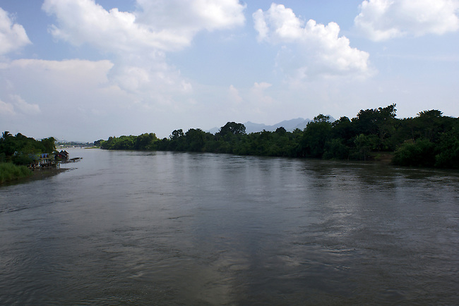 A lovely cloud-filled, blue sky rises above a tree-lined section of the River Kwai (Khwae Yai) taken from the railway bridge - the actual Bridge on the River Kwa - that spans the river. .