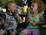Garrett Ugolik 1 1/2 of Enfield, and his sister Morgan, 3, try somewhat unsuccessfully to eat their ice cream cones as the 90 degree temperatures makes for a melt down, Friday, July 5, , 2013, at the Taste of Enfield, part of the annual July 4th celebration on the town green, the celebration runs through Sunday. (Jim Michaud / Journal Inquirer)