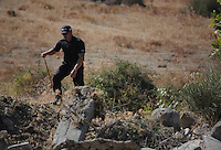 Pictured: A police officer involved with clearing the new site of the search, where rubble was deposited from the farmhouse where Ben Needham disappeared from in Kos, Greece. Thursday 06 October 2016<br />