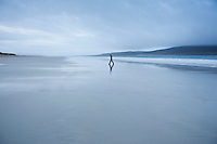 Woman walks along Luskentyre beach on overcast day, Isle of Harris, Western Isles, Scotland