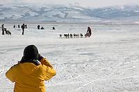 A fan takes a picture of Lance Mackey approaching Unalakleet. Photo by Jon Little.