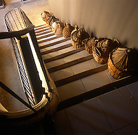 A view from above of a staircase with tiled treads. A line of baskets are placed on one side of each step.