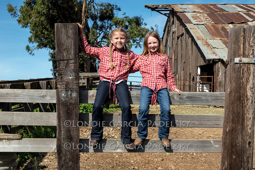 Myla and Lyla sitting on the corrals at the barn