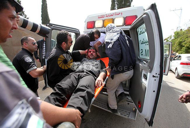 Palestinian medics carry a wounded protester during clashes with Israeli security forces following a protest Palestinian Prisoner's Day and against the expropriation of Palestinian land by Israel in the West Bank village of Kafr Qaddum, near the northern city of Nablus, April 17, 2015. The current number of Palestinians held in Israeli prisons is at least 6,200 and is the biggest for at least five years, according to figures from rights groups. Photo by Nedal Eshtayah