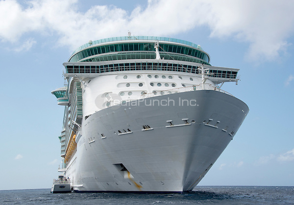 The Royal Caribbean Freedom of the Seas, which carries 4,515 passengers and 1,360 crew, and the Celebrity Reflection, which carries 3,609 passengers and 1271 crew, in the harbor of George Town, Grand Cayman in the Cayman Islands on Tuesday, December 20, 2016.  The smaller boat alongside the ship is a tender to ferry passengers back and forth to the island.<br /> Credit: Ron Sachs / CNP /MediaPunch
