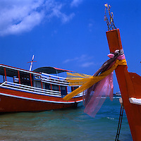 Religious scarfs and flowers on fishing boat at Pattaya beach,Thailand.